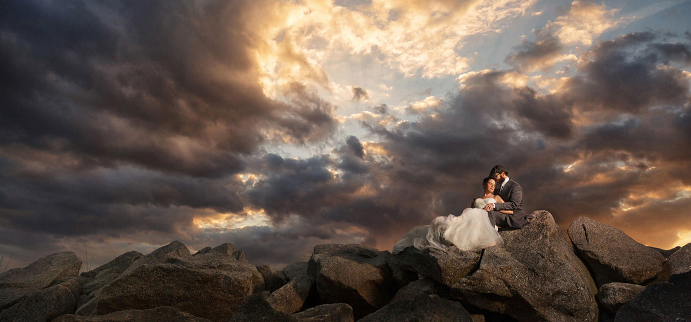 Bride and groom on rocks in Charleston SC with dramatic sunset