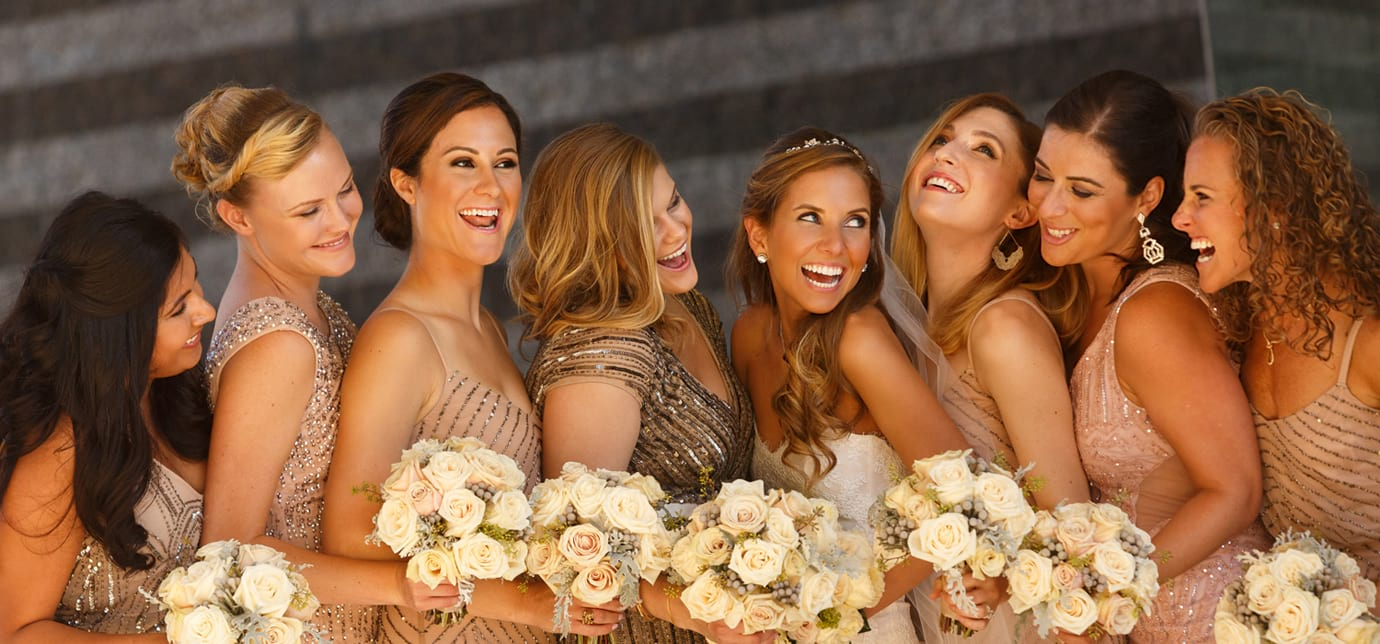 Bridesmaids huddle and laugh with their bouquets